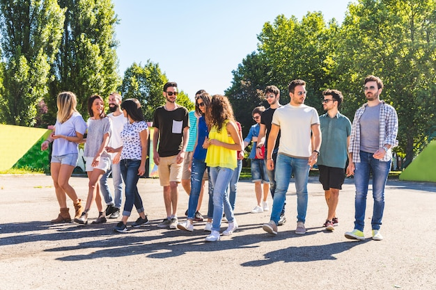 Grande gruppo di amici che camminano insieme al parco