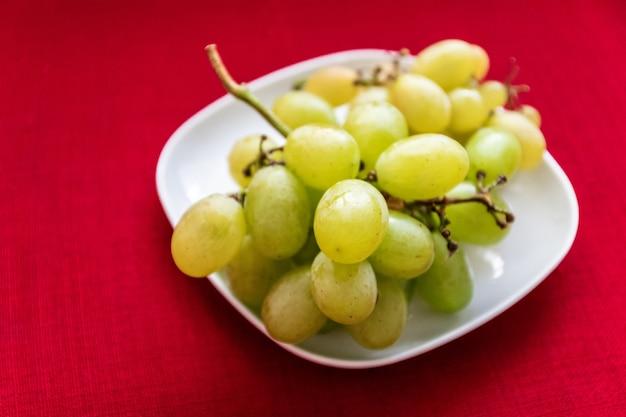 Grande gustosa uva dolce su un piatto bianco