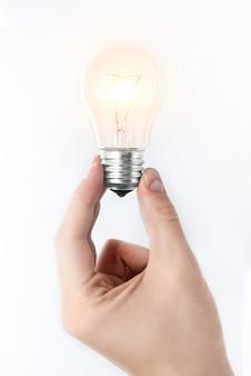 Grande idea concetto la mano dell'uomo che tiene una lampadina incandescente su uno sfondo bianco