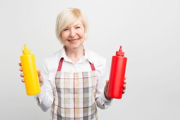 Grande immagine dell'anziana che tiene in mano due bottiglie di sauses. vuole cucinare del cibo gustoso per la sua amata.
