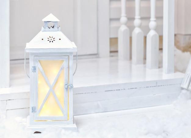 Grande lampada di via bianca d'annata che sta sul portico con neve