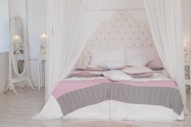 Grande letto con biancheria da letto pastello nella stanza della donna