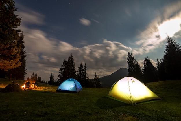 Grande luna luminosa in cielo nuvoloso blu scuro sopra due tende turistiche sulla foresta erbosa verde.