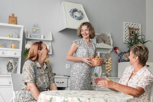 Grande madre e madre che esaminano figlia sorridente che tiene canestro di vimini del croissant