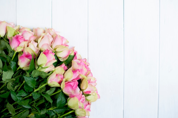 Grande mazzo di rose con petali di rosa e verde su fondo di legno bianco