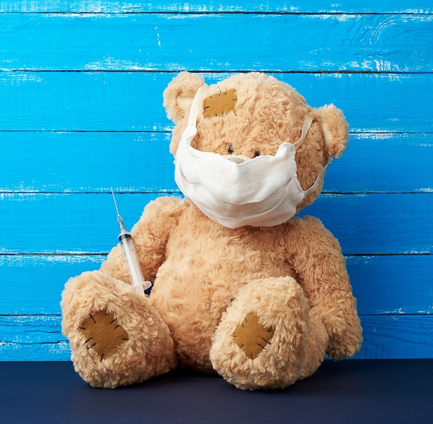 Grande orsacchiotto beige con le toppe che si siedono in una mascherina medica bianca con una siringa nella sua zampa