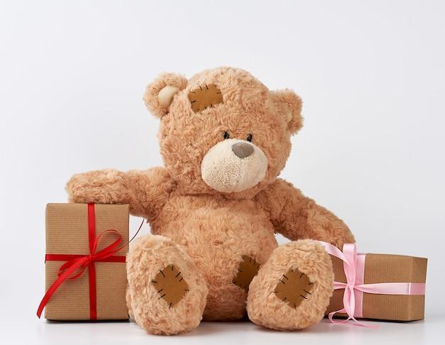 Grande orsacchiotto beige con toppe, una pila di regali in scatole avvolte in carta marrone, legato con nastro di seta su un bianco
