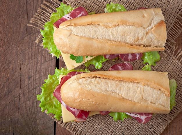 Grande panino con carne affumicata cruda su una superficie di legno