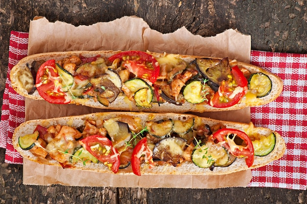 Grande panino con verdure arrosto (zucchine, melanzane, pomodori) con formaggio e timo su fondo in legno vecchio
