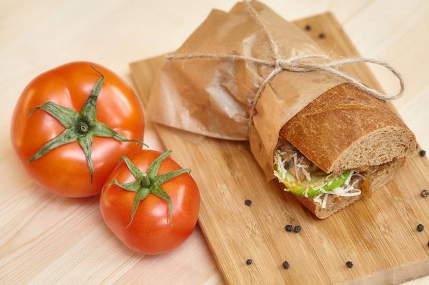 Grande panino sul tagliere di legno con ingredienti