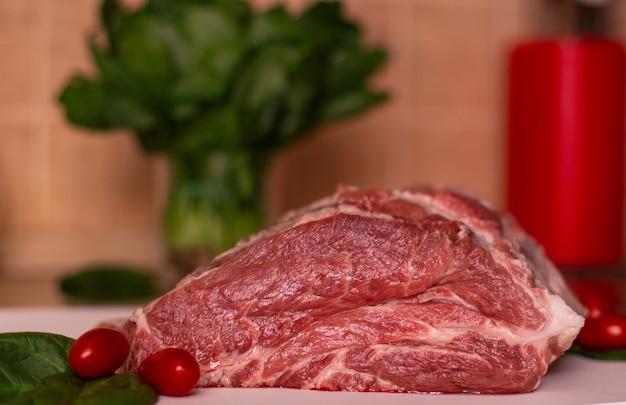 Grande pezzo di carne di maiale cruda rossa, pomodorini e verde