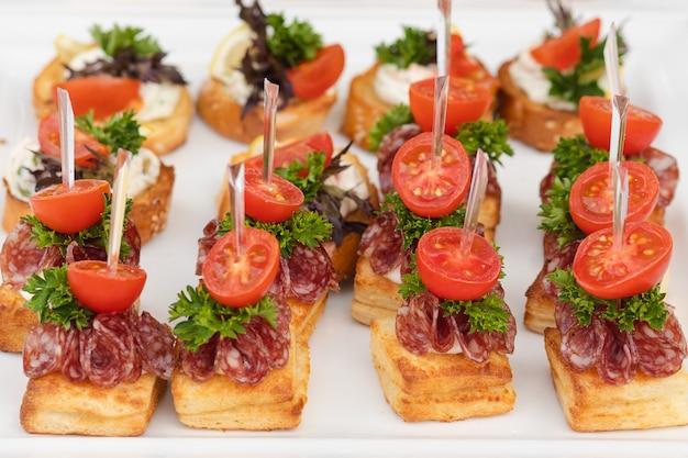 Grande piatto del primo piano con il prezzemolo e il salame del pomodoro del pane fritto canape dello spuntino serviti
