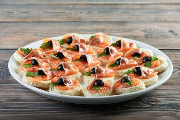 Grande piatto pieno di tartine con salmone e burro decorato con olive nere poste sulla fame di appetito antipasto ristorante tavolo in legno mangiare cibo delizioso spuntino.