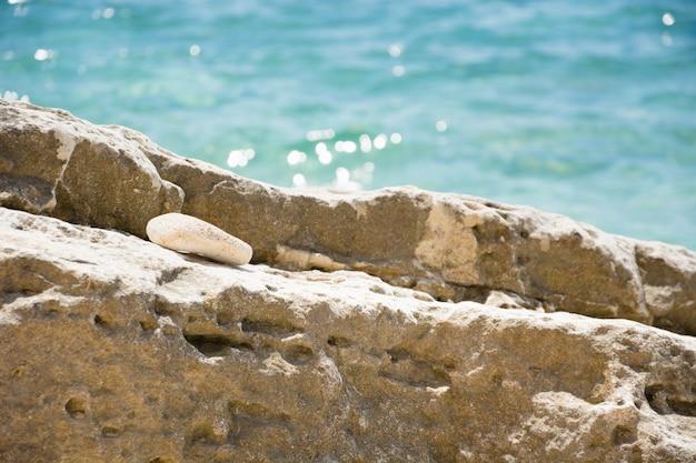 Grande pietra sulla spiaggia selvaggia. concetto di vacanza estiva costa