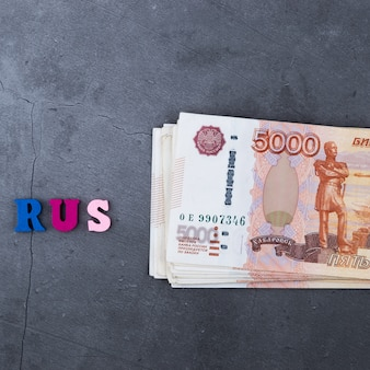 Grande pila di banconote russe dei soldi di cinquemila rubli che si trovano su una priorità bassa grigia