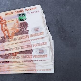 Grande pila di banconote russe dei soldi di cinquemila rubli che si trovano sul cemento grigio.