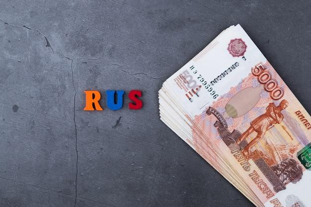 Grande pila di banconote russe dei soldi di cinquemila rubli che si trovano sul fondo grigio