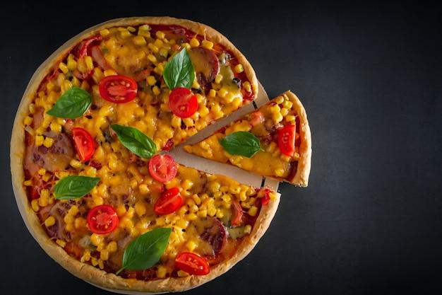Grande pizza italiana con i pomodori e basilico sul nero