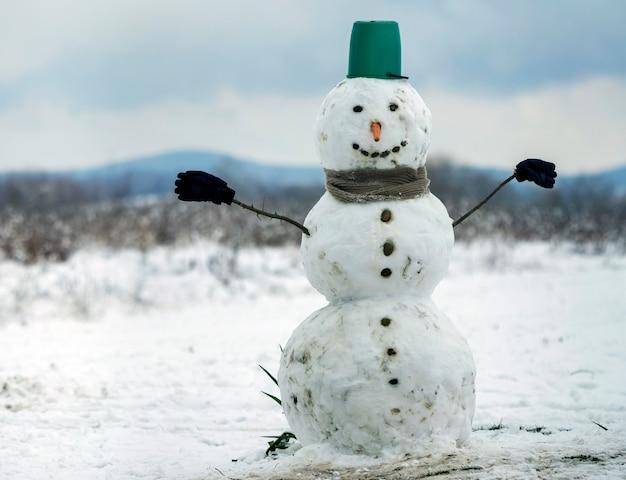 Grande pupazzo di neve sorridente con cappello secchio, sciarpa e guanti sul paesaggio invernale campo nevoso bianco