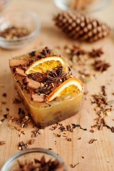 Grande saponetta fatta a mano con bastoncini di cannella, anice stellato e fette d'arancia su un tavolo di legno con spezie grattugiate nelle vicinanze