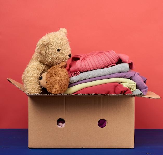 Grande scatola di cartone marrone piena di vestiti e giocattoli per bambini