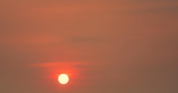 Grande sole rotondo e cielo rosso al tramonto la sera con spazio per la citazione di ispirazione.