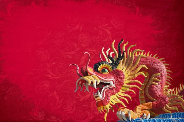 Grande statua rossa del drago sul fondo rosso di struttura.