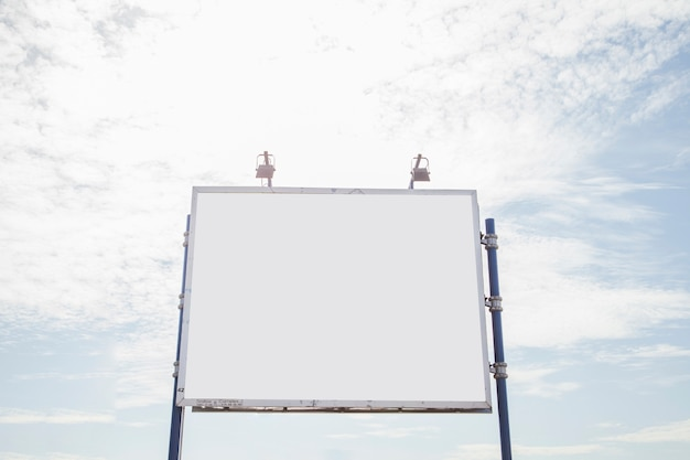 Grande tabellone per le affissioni vuoto con due lampada contro il cielo