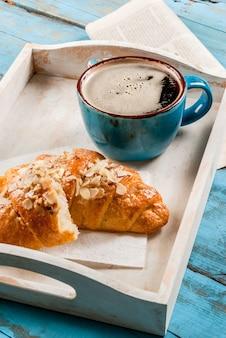 Grande tazza da caffè, cornetto e giornale