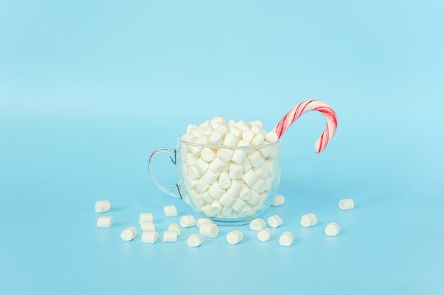 Grande tazza trasparente di marshmallow con canna da lecca-lecca rossa sulla parete blu. buon natale o felice anno nuovo concetto.