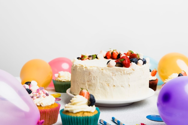 Grande torta con bacche diverse vicino a mongolfiere