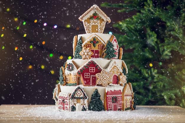 Grande torta natalizia a più livelli decorata con biscotti di panpepato e una casa in cima. sfondo albero e ghirlande.