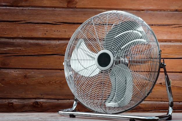 Grande ventilatore da tavolo sul tavolo sullo sfondo di una parete di legno