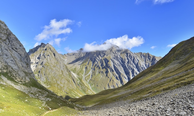 Grande vista sul fondo della montagna delle cime rocciose sotto cielo blu