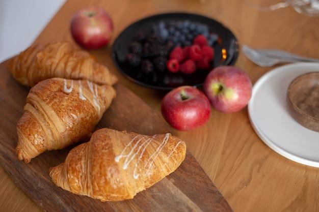 Grandi cornetti, bacche, mele rosse su un tavolo di legno