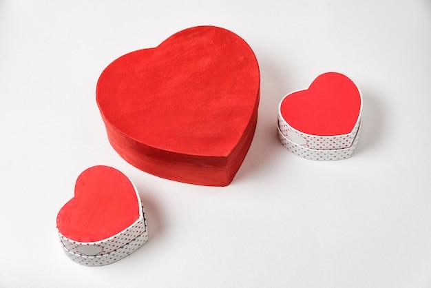 Grandi e due piccole scatole a forma di cuore rosso sul tavolo. sopra la vista. san valentino