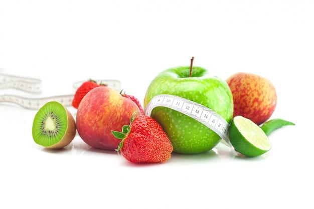 Grandi fragole rosse succose mature, mela, lime, pesca, kiwi e nastro di misurazione