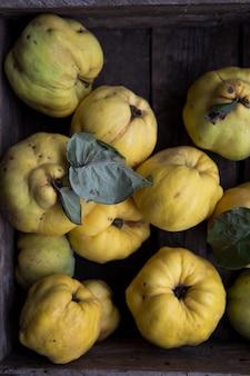 Grandi frutta e fetta mature della cotogna con fogliame verde nel tardo autunno sulla tavola di legno marrone. vista dall'alto