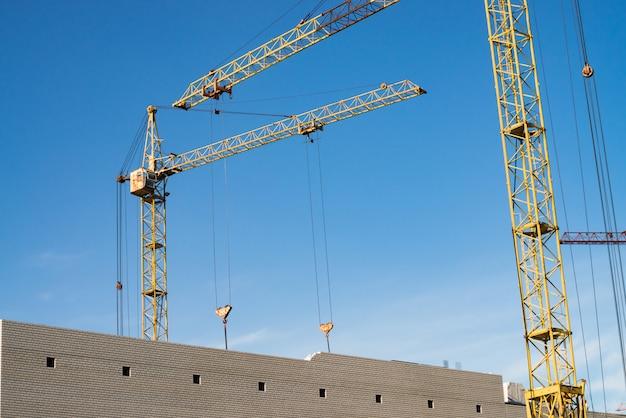 Grandi gru a torre sopra gli edifici in costruzione contro il cielo blu. immagine del primo piano della costruzione con lo spazio della copia. costruire della città.