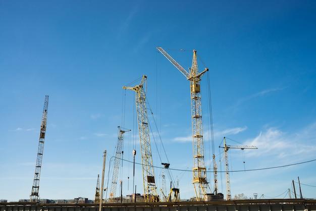 Grandi gru a torre sopra gli edifici in costruzione contro il cielo blu. immagine di sfondo del primo piano della costruzione con lo spazio della copia. costruire della città.