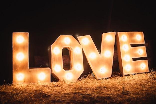 Grandi lettere con lampadine in un matrimonio notturno