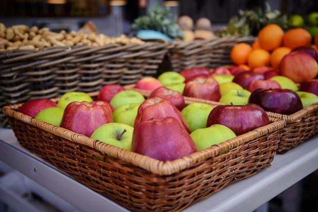 Grandi mele rosse e verdi luminose in un cestino