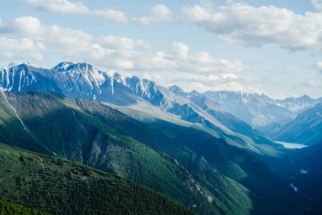 Grandi montagne, ghiacciai e valle della foresta verde con lago alpino e fiume.