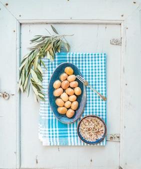 Grandi olive verdi in piatto ceramico rustico con il ramo di albero e le spezie sull'asciugamano di cucina sopra blu-chiaro