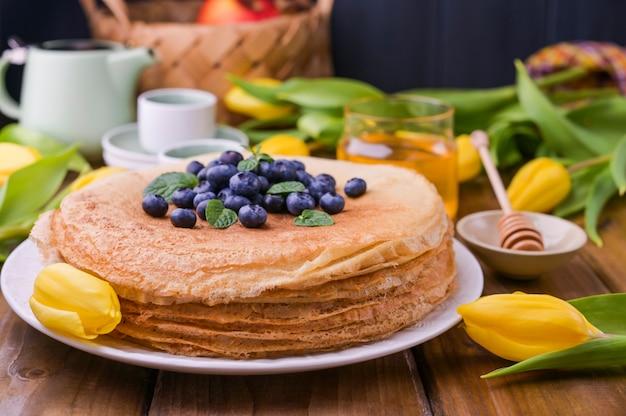 Grandi pancake russi tradizionali con bacche e miele su un tavolo di legno. cottura per le vacanze di primavera shrovetide e un mazzo di tulipani gialli. copia spazio.