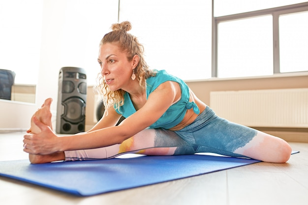 Grandi progressi. giovane bella donna in abiti sportivi che fanno allungamento davanti alla finestra in palestra