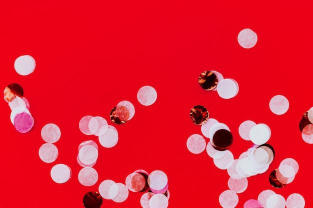 Grandi punti glitter che volano scintillii su sfondo rosso alla moda audace. sfondo festivo per progetti di graphic design con spazio per il testo.