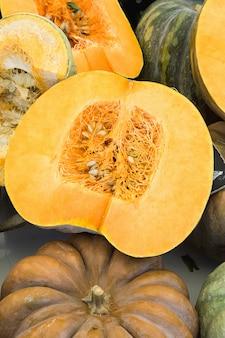 Grandi zucche variopinte arancio scuro e verdi grandi intere e divise in due.