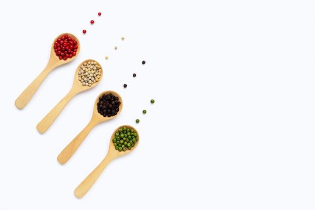 Granelli di pepe bianchi e neri verdi, rossi con il cucchiaio di legno su bianco