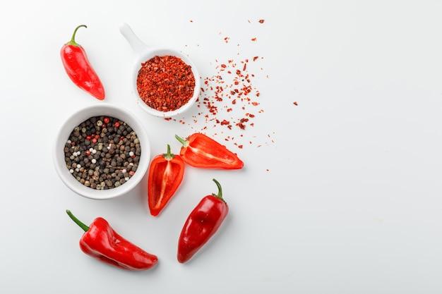 Granelli di pepe con la polvere di peperoncino rosso in mestolo e peperoni in un piatto sulla parete bianca, vista superiore.